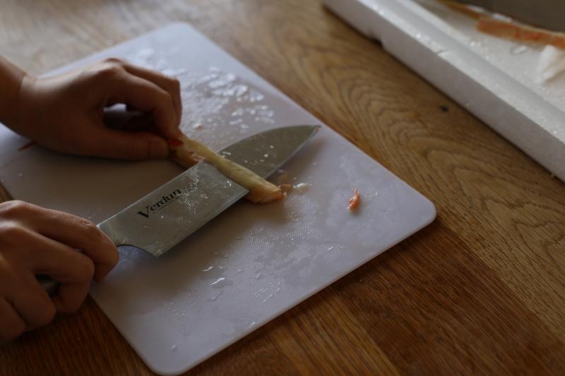 包丁をスライドしてズワイガニの足の皮を切る